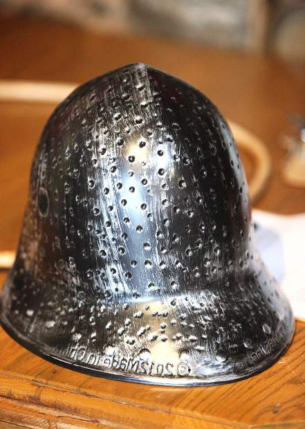 A metal looking helmet is fitting attire for children, teachers, and parent volunteers that gathered to make the Medieval Feast a success for its 29th year.