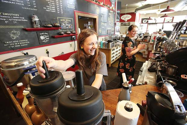 Caroline's baristas Glory Rain and Kelsey Anderson make drinks for customers Thursday in downtown Grass Valley during Pay With a Poem Day, where folks could get a cup of coffee in exchange for writing a poem .