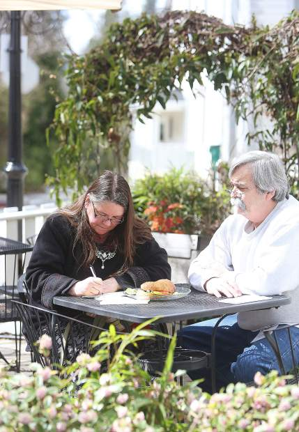 Nevada City's Lynlee Lyckberg works on crafting a poem from the courtyard of Broad Street Bistro in celebration of World Poetry Day Thursday, next to her husband Glenn. Folks were asked to create a poem of 30 words or less and were treated with a free cup of coffee from one of four participating coffee shops including Foxhound, Caroline's, Fable and Broad Street Bistro. Poems were displayed at each establishment, and will be included in the Sierra Poetry Festival on April 27.