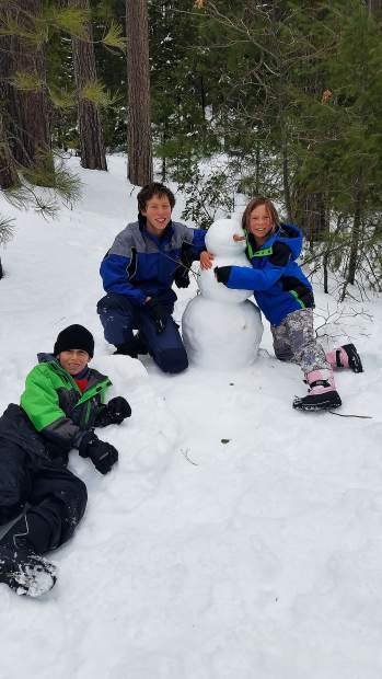 Kids playing in the snow off Highway 20.