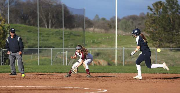 Bear River short stop Julia Vaughn fields a Lady Miners at bat while a Nevada Union baserunner makes her way towards third base.