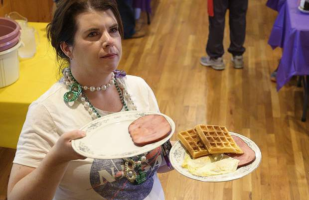 Rachel Cleveland awaits a few more waffles before serving dozens of customers Tuesday.