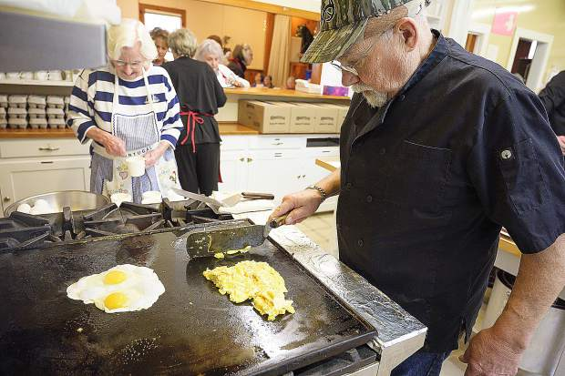 Jerry DeRego cooks up a batch of eggs, while Julie Barker assists in the kitchen.