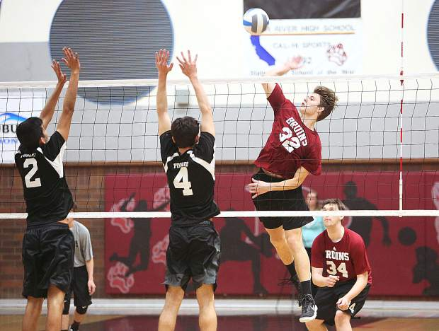 Bear River sophomore Jace Rath smashes a spike over the net towards a pair of Pioneer High School defenders during Tuesday's win in three straight sets over the Patriots.