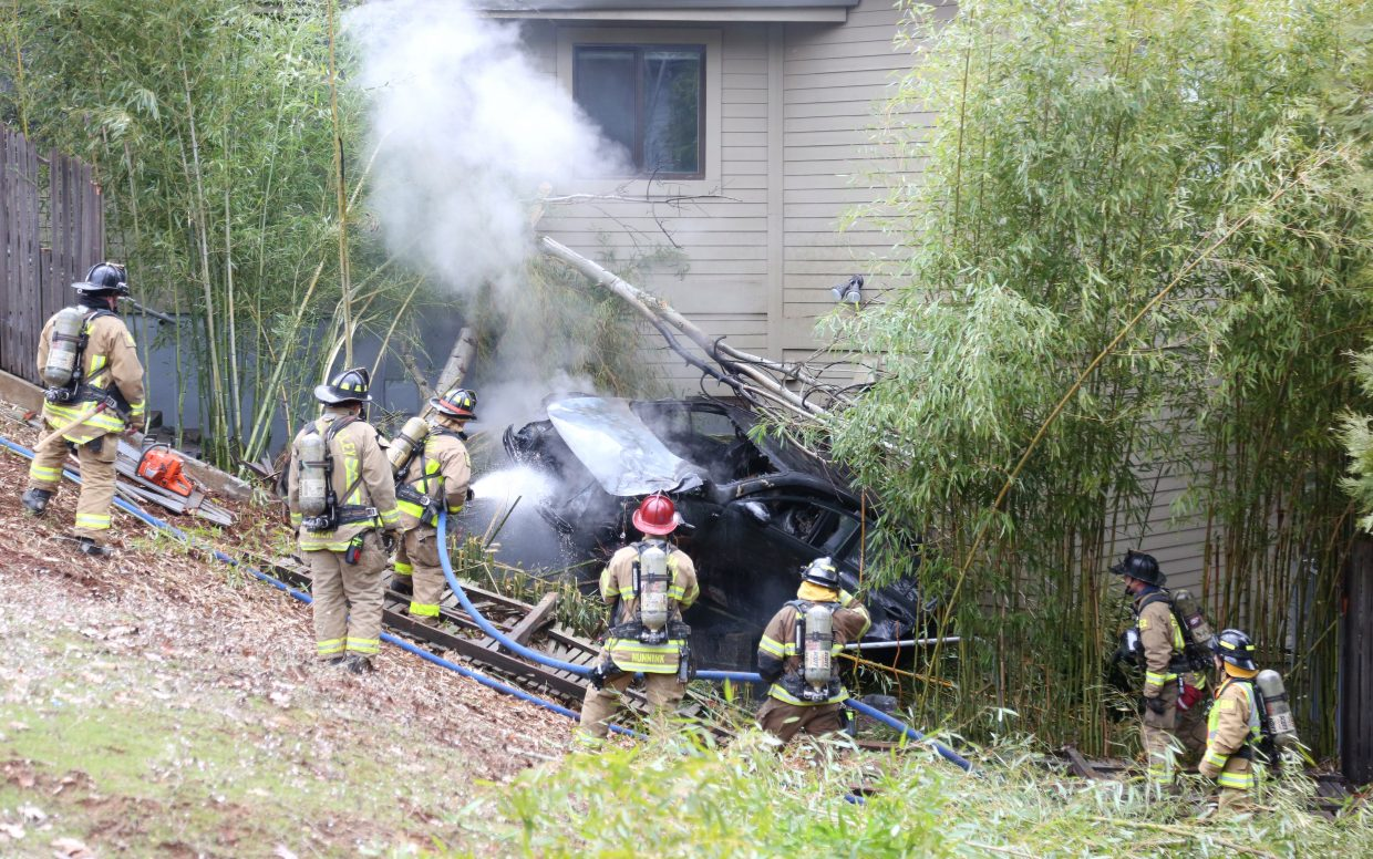 A vehicle careened off of Ventana Sierra Drive and into a home before catching fire in the Morgan Ranch area of Grass Valley Friday afternoon. -- Photo by Elias Funez/efunez@theunion.com