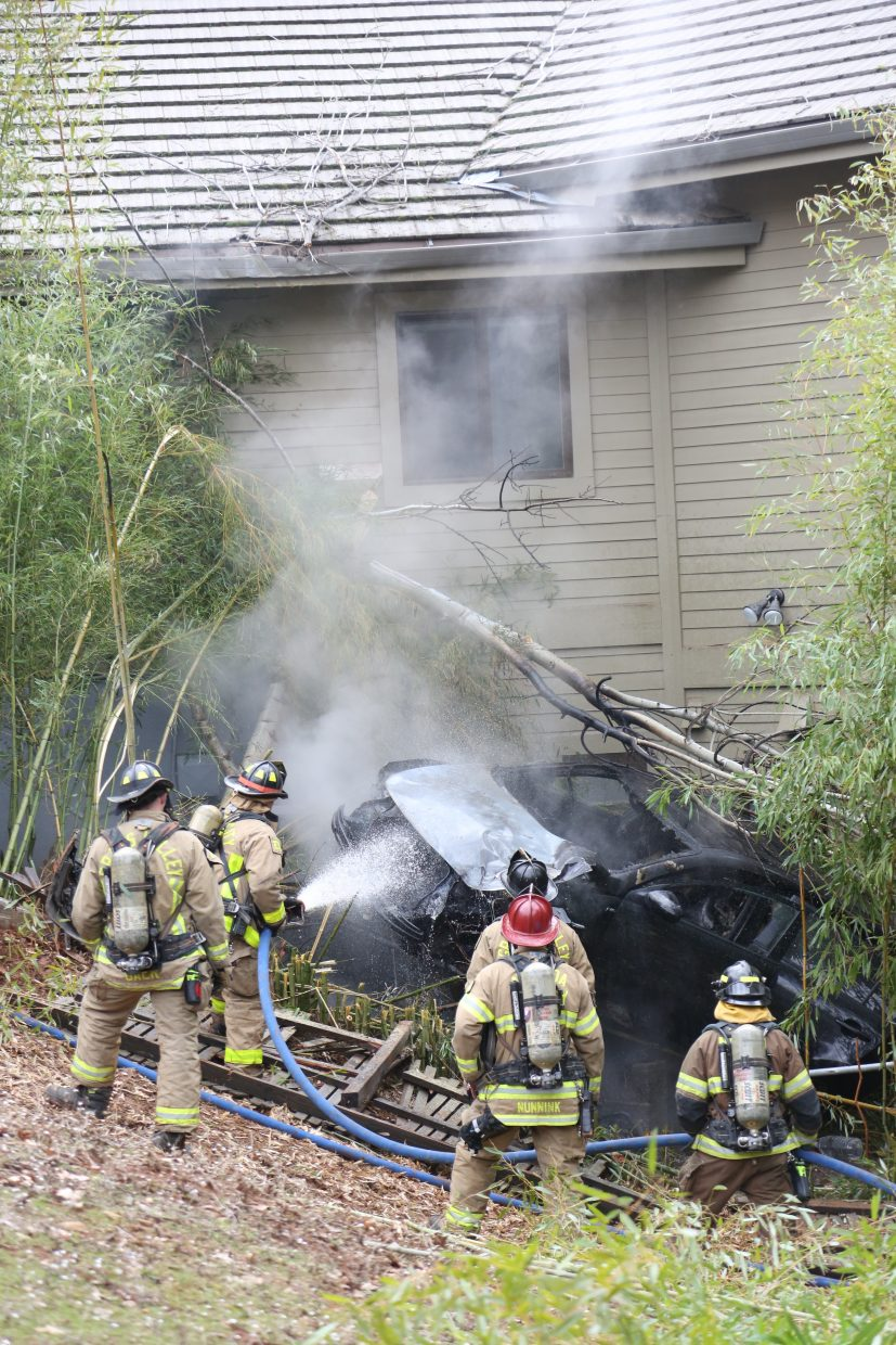 Smoke dissipates into the air as firefighters douse the engine bay of a Kia vehicle that caught fire after colliding with a home Friday off of Ventana Sierra Drive.