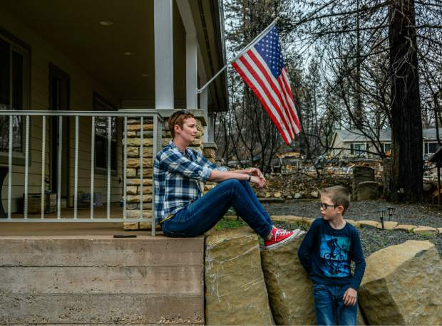 In this photo taken March 19, 2019, Dawn Herr and her son Liam, 8, visit their home in Paradise, Calif., that survived the Camp Fire. The Herrs' home, built in 2010, was scorched and had smoke damage inside so the family is living temporarily in nearby Chico. The Herrs credit the home's survival to strict building codes and to gravel that encircled the building and kept the flames back. (Hector Amezcua/The Sacramento Bee via AP)