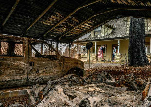 In this March 19, 2019, Sean and Dawn Herr collect an American flag that survived the Camp Fire along with their Paradise, Calif., home. The Herrs' home, built in 2010, was scorched and had smoke damage inside so the family is living indefinitely in nearby Chico. The Herrs credit the home's survival to strict building codes and to gravel that encircled the building and kept the flames back. (Hector Amezcua/The Sacramento Bee via AP)