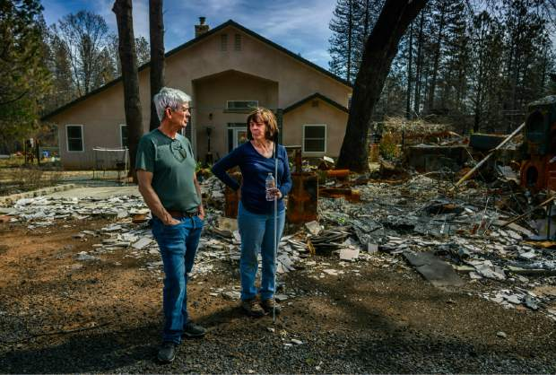 In this March 19, 2019 photo, Oney and Donna Carrell stand near the ashes of her father's house in Paradise, Calif. Their property had two homes on it before the fire, but the only one to survive visible behind them was built to fire-resistant standards that went into effect in 2008. (Hector Amezcua/The Sacramento Bee via AP)