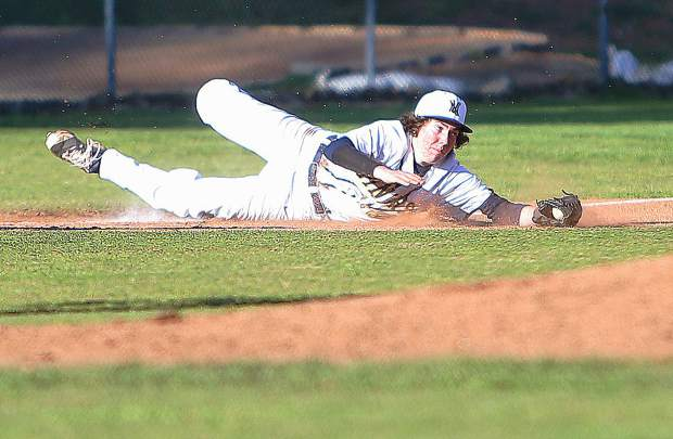 The varsity Miners' third baseman makes a diving stop of a Ponderosa hit during Thursday's win.