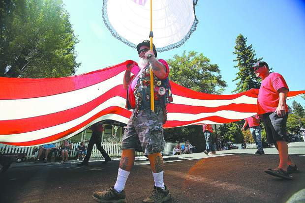 Local E. Clampus Vitus members help carry the large U.S. flag through the streets of downtown Nevada City during the annual Constitution Day Parade Sunday.