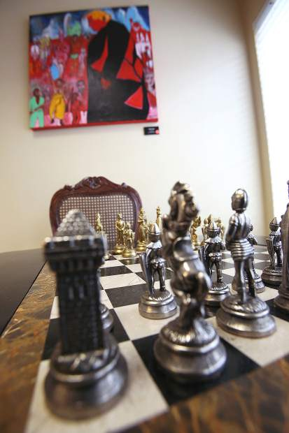 A chess board with ornate pieces sits ready for a game under a Ron Kenedi painting at the Courtyard Suites in downtown Grass Valley.