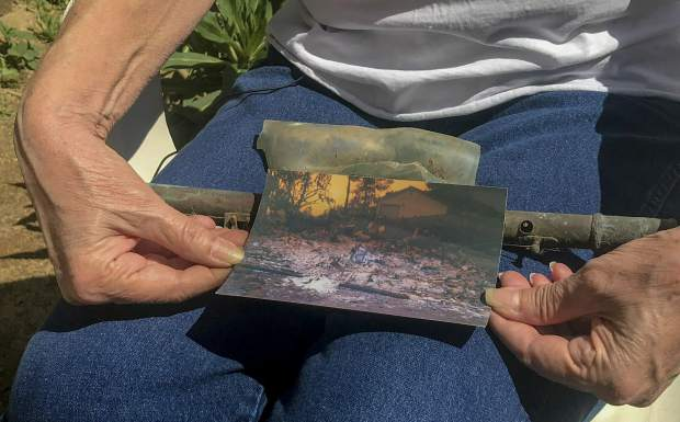 In this March 22, 2019, photo, Cheri Skipper, a Harbison Canyon resident, holds her burned flute and a picture showing what her home looked like after it burned during the Cedar Fire in 2003. Every 30 years or so, a massive fire blows through Harbison Canyon, 30 miles northeast of San Diego. The 1970 Laguna Fire destroyed much of the unincorporated town that sits inside the canyon and shares its name. Harbison Canyon was rebuilt again after the Cedar Fire burned through in 2003, destroying 287 of the 388 homes. (Ryan Sabalow/The Sacramento Bee via AP)