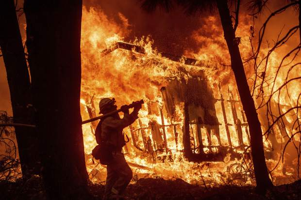 FILE - In this Friday, Nov. 9, 2018 file photo, firefighter Jose Corona sprays water as flames from the Camp Fire consume a home in Magalia, Calif. More than 2.7 million Californians live in areas that are at very high risk for wildfires. One in 12 homes in California are at high risk of burning in a wildfire. The more information we can share about where and how we're falling short, the quicker we can come together on potential solutions. (AP Photo/Noah Berger, File)