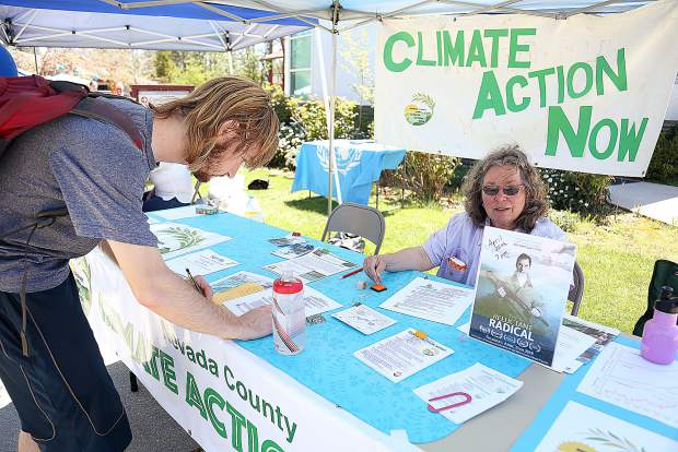 Sierra College student Skyler Cotton fills out information after talking to Debbie Gibbs at the Nevada County Climate Action Now booth last week during Sierra College's Earth Day and Health Fair event. The climate action group is pushing for the county to be on 100% renewable energy.