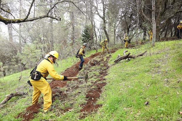 Firefighters work on cutting a fire break line during the Lake of the Pines fire preparedness drill Saturday.