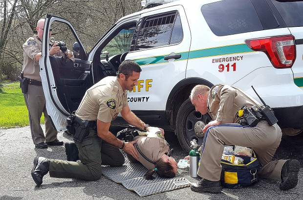 Nevada County Sheriff's Deputy Chris Stanio, left and California Highway Patrol Officer Jason Morgan tend to Deputy Kristin Morgan, portraying an officer who has been critically injured by a gunshot, in a scenario played out during the drill in Lake of the Pines Sunday.
