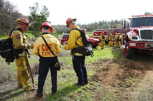 Firefighters confer on their assignment during Sunday's Lake of the Pines multi agency fire preparedness drill. Another fire drill is being planned for May 5 at the Rood Government Center.