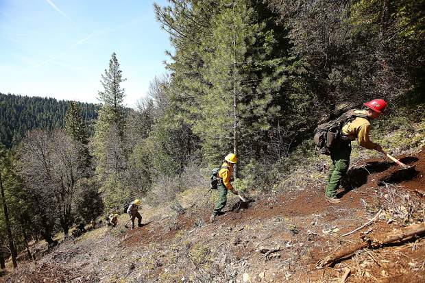 Prospective wildland firefighters create a fire break line down a steep hill behind the White Cloud fire station during Wednesday's Work for Warriors field training.
