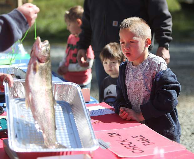 Six-year-old Josiah Littlehawk Ortiz watches closely as his 3.8-pound, 20-inch trout is weighed by event officials.