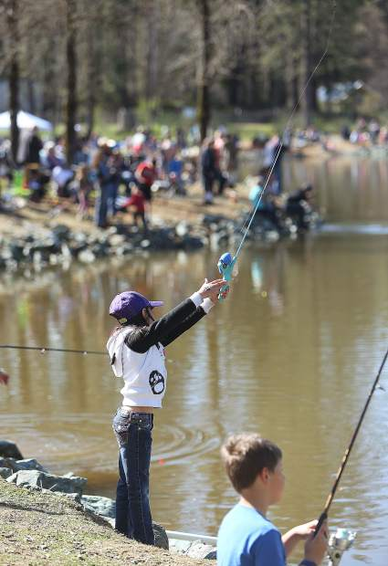 Seven-year-old Addison Hale casts her own line out onto Lions Lake during Saturday's annual trout fishing derby.