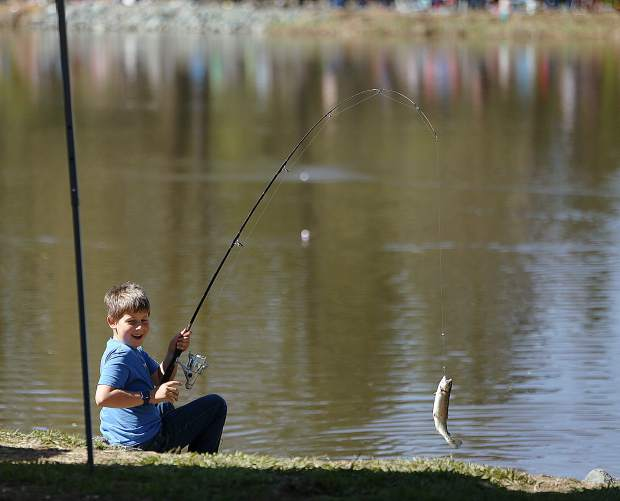 A happy young fisherman pulls a trout out of Lions Lake during Saturday's trout derby.