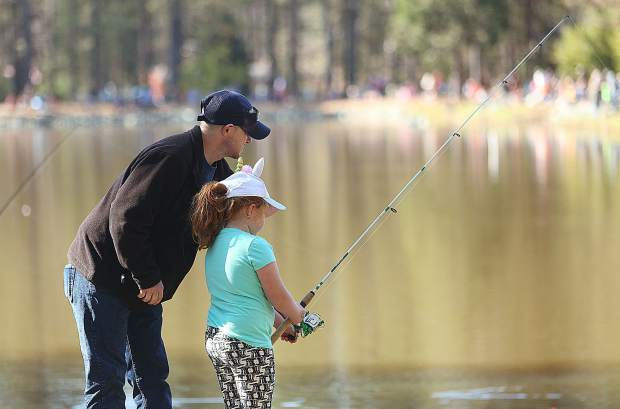 A young fisherwoman gets some pointers during the trout derby.