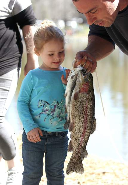 Participating in her first trout derby Kambree Colen, 3, and uncle Brian Estrada show off her large trout catch.