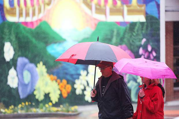 Grass Valley's Dan and Tina Hauck don their umbrellas as they walk across Main Street at Mill Street in downtown Grass Valley during rain showers Tuesday April 2.