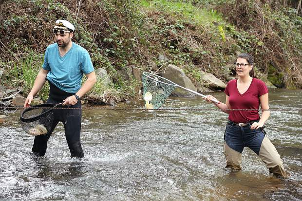 Tom and Kate Ivy catch the paper boats during the Wolf Creek Alliance boat races Sunday April 7 behind Wild Eye Pub.