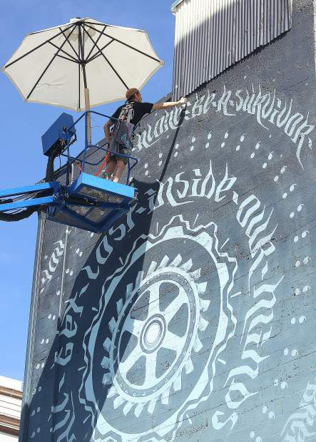 Miles Toland works on the new downtown Grass Valley mural titled