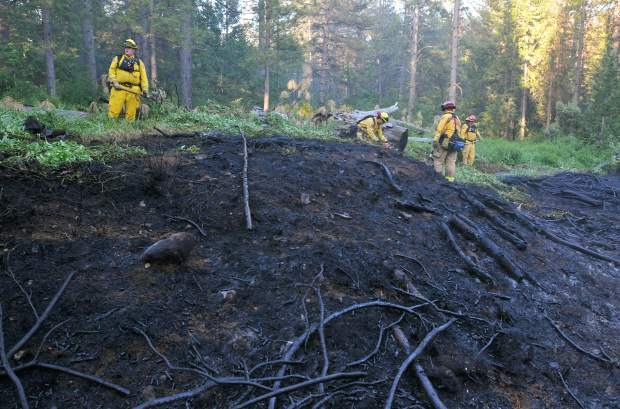 A crew of Calfire firefighters work to contain a blaze that spread into Empire Mine State Historic Park from Stacey Lane after a structure caught fire in May of 2017. Residents of the Gold Hill neighborhood, which also borders Empire Mine, are concerned that excess dead trees and vegetation within the park will fuel a wildfire that could consume their homes.