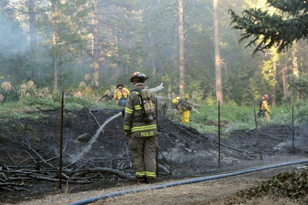 A crew of Cal Fire firefighters work to contain a blaze that spread into Empire Mine State Historic Park from Stacey Lane after a structure caught fire in May of 2017. Residents of the Gold Hill neighborhood, which also borders Empire Mine, are concerned that excess dead trees and vegetation within the park will fuel a wildfire that could consume their homes.