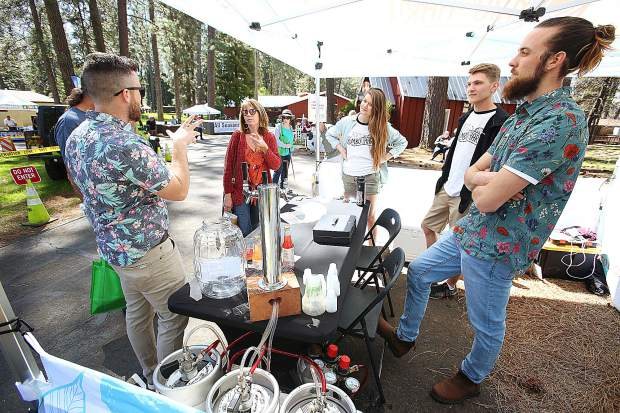 Brothers Sean Miller (left) and Patrick Miller (right) talk to a group of folks perusing the Home and Garden Show Saturday at the fairgrounds.and offering tastes from their NC Kombuchary selection.