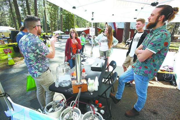 Brothers Sean Miller (left) and Patrick Miller (right) talk to a group of folks perusing the Home and Garden Show Saturday at the fairgrounds.
