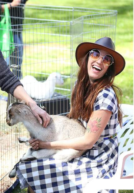 Erin Kaiser of New Wellington Farms off of Bitney Springs Road, holds a baby goat named Liam as folks stop by and learn about the farm and the many uses of the goats.