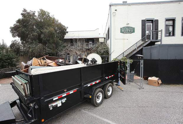 A junk hauling company loads a trailer with furniture and items from Grass Valley's Holbrooke Hotel, which closed earlier this year, to accommodate remodeling efforts.