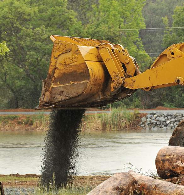 A front-end loader spreads gravel along a pathway around Lions Lake at the Nevada County Fairgrounds Wednesday. The lake is closed until the restoration process is completed.