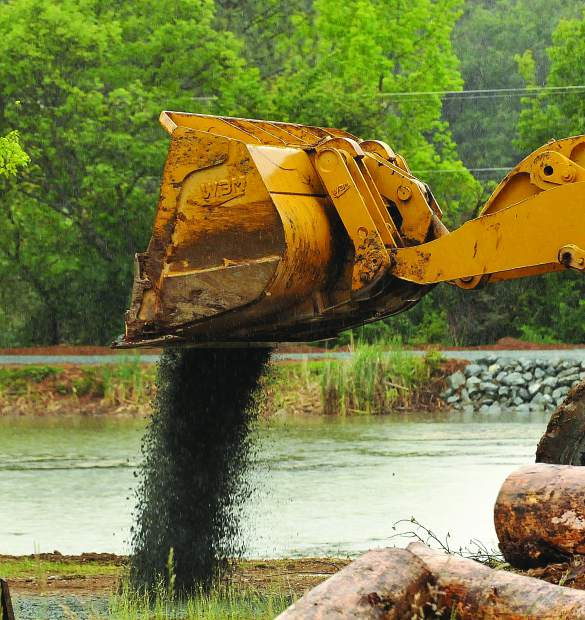 A front end loader spreads gravel along a pathway around Lions Lake at the Nevada County Fairgrounds Wednesday. The lake is closed until the restoration process is completed.