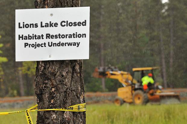 Signs and caution tape inform that Lions Lake is closed at the Nevada County Fairgrounds due to a habitat restoration project.