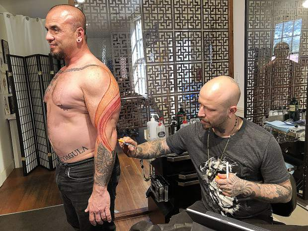 Tattoo artist Judicael Vales maps out a new tattoo on client Thao Hill. Previous work was done by other artists.