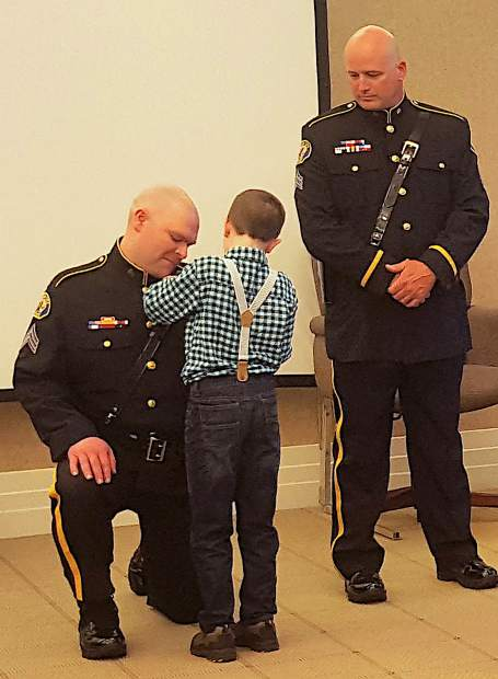 Matthew Holdcroft pins a badge on his father, Nevada City Police Sgt. Luke Holdcroft, as Sgt. Sean Mason looks on, during their promotion Wednesday.