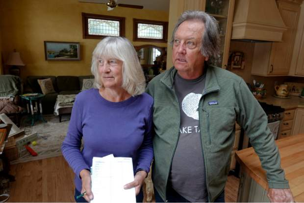 Laura and Ed Haneveld stand in their Olympic Valley home with a checklist of items they'd try to save during a wildfire. The couple worries a proposal to add hundreds of homes and nearly 300,000 square feet of commercial development at Squaw Valley Resort could hinder an evacuation.