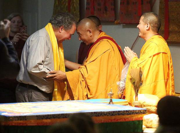 Sierra Friends of Tibet's Joseph Guida is blessed by the monks of the Gaden Shartse Monastery with a golden sash before the dissolution ceremony of the sand mandala March 9.