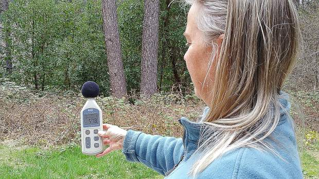 East Bennet Road resident Heidi Zimmerman holds a decibel sound reading meter indicating 58.6 decibels of sound from Rise Gold's exploratory drilling heard from her bedroom window.