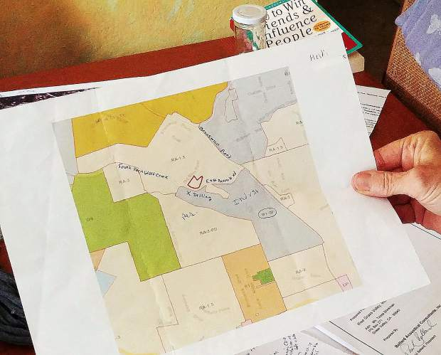 East Bennet Road resident Heidi Zimmerman shows a map outlining her property in red and Rise Gold Corp's land holdings in grey. Zimmerman says the round-the-clock drilling is impacting her life.