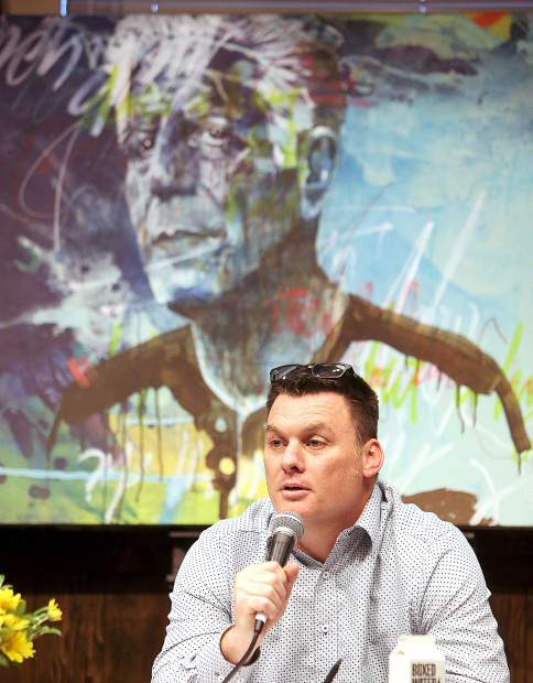 Nevada County Behavioral Health Clinical Supervisor Curtis McMullan speaks as a panelist during the Suicide Awareness Town Hall Forum at KVMR's community room Tuesday evening. A portrait of Anthony Bourdain painted by Dylan Telleson is situated behind the panel.