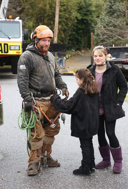 Flying Squirrel tree climber Rick Savalin is greeted by his daughter and wife after finishing his portion of climbing and cutting of the 180-foot tree.
