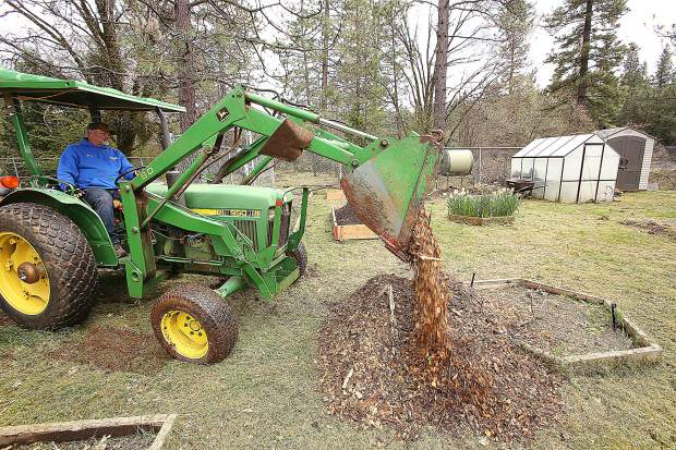 School staff member Doug Rice utilizes a tractor to transport bark to be spread around the planter boxes at Union Hill School's garden.
