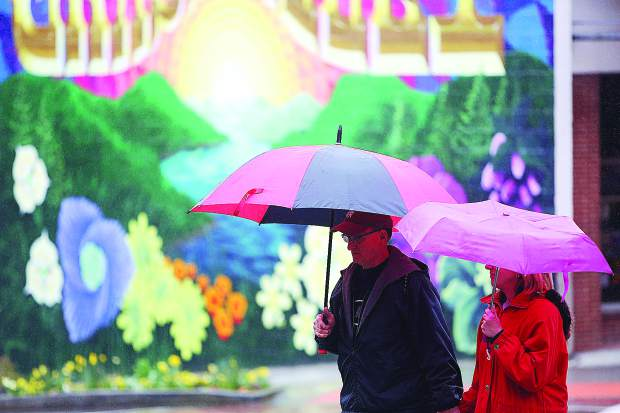 Grass Valley's Dan and Tina Hauck don their umbrellas as they walk across Main Street at Mill Street in downtown Grass Valley Tuesday. Rain showers are expected through the week at least until Sunday.